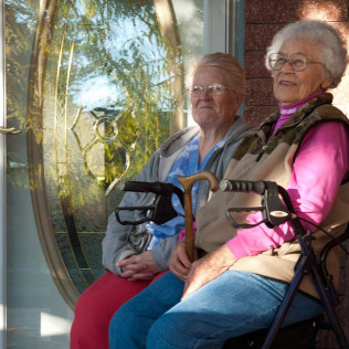 2 elderly ladies laughing outside on a porch at Gooding, ID assisted living facility
